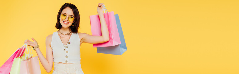 panoramic shot of happy fashionable girl in sunglasses holding shopping bags isolated on yellow