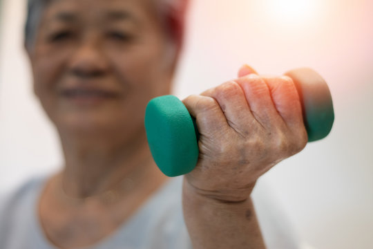 Senior elderly Asia woman hand holding dumbbell in physical therapy session. Healthy old people concept.
