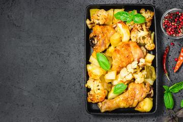 Roasted chicken and vegetables on cast iron skillet, dark background. Top view, space for text.