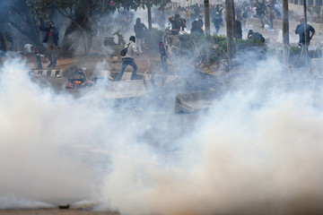 Protesters run as riot police fire tear gas during a riot following protests near Indonesian Parliament building in Jakarta