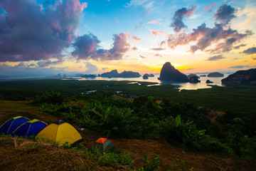 Camping tent on hill of mountain sunrise sea bay
