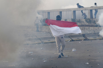 A protester holds Indonesian flag as riot police fire tear gas during a riot following protests near Indonesian Parliament building in Jakarta