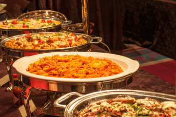 Penne with tomato sauce, roast chicken, and other food served in chafing dishes at a buffet party