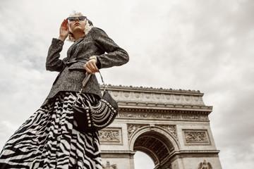 Outdoor autumn fashion portrait of elegant, luxury lady wearing trendy boucle blazer, animal, zebra print pleated midi skirt, holding baguette bag, posing near Triumphal Arch in Paris. Copy space