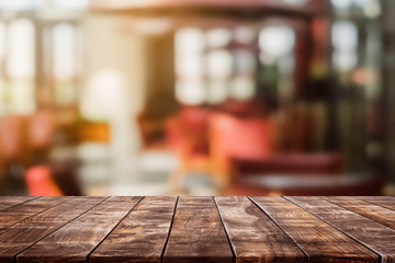 Empty wood table top and blurred coffee shop and restaurent interior background - can used for display or montage your products.