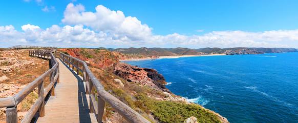Spoed Fotobehang Blauw traumhaft schöner Küstenwanderweg mit Holzsteg an der Costa Vicentina, Algarve Portugal