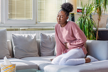 Young black woman suffering from stomachache on sofa at home. Woman sitting on bed and having stomach ache. Young woman suffering from abdominal pain while sitting on sofa at home
