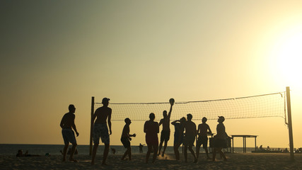 People play volleyball on the beach at sunset. Friends playing volleyball on a beach during sunset. Summer vacation concept.