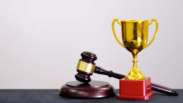 Judge's gavel and trophy on white background. Symbol for jurisdiction. Law concept a wooden judges gavel on table in a courtroom or law enforcement office