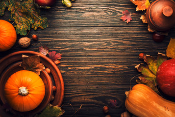 Thanksgiving dinner place setting. Autumn fruit, pumpkins, nuts, fallen leaves with plate and cutlery. Thanksgiving autumn background