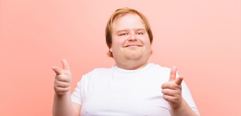 young big size man feeling happy, cool, satisfied, relaxed and successful, pointing at camera, choosing you against pink wall Papier Peint