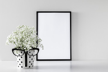Black frame photo on white wood table and small white flowers in vase. White gypsophila flowers on shelf or desk. Mock up with decor elements.