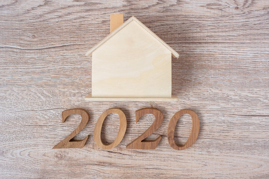 2020 Happy New Year with house model on wood table background with copy space. Financial, money, refinance, Real estate and new hone concept