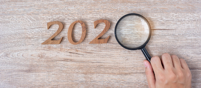 2020 Happy New year with Businessman holding glass magnifying and wooden number on table. New Start, Vision, Resolution, Strategy, Goals, Mission and Search Engine Optimization concept