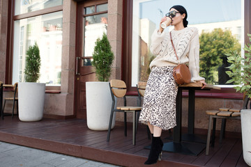 fashion woman in sunglasses and a warm knitted sweater is drinking coffee. Urban atmosphere