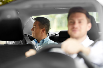 transportation, taxi and people concept - middle aged male passenger on back seat and car driver
