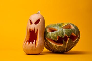 Image of two creepy halloween pumpkins on empty orange background.
