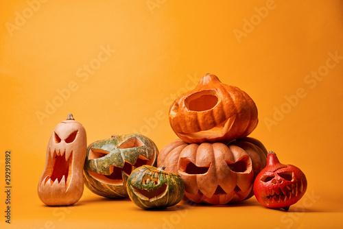 Photo of creepy halloween pumpkins on empty orange background.