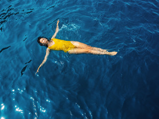 young woman in a one-piece yellow swimsuit floats on the surface of the water.