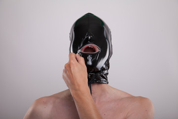 man wears black shiny latex mask on his head opening metal zipper over mouth