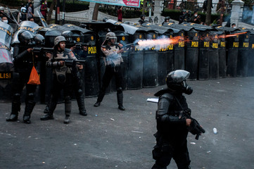 Riot police officers fire tear gas during a protest outside local parliament building in Bandung