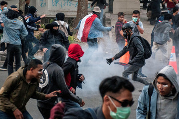 Protesters run as riot police fire tear gas during a riot following protests outside local parliament building in Bandung