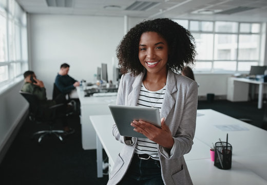 Portrait of a smiling confident african american young businesswoman holding digital tablet in hand looking at camera with colleague at background in office