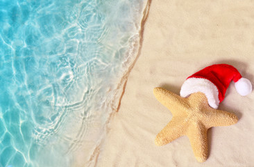 Christmas holidays concept. Top view of starfish in santa claus hat on summer sand beach.