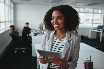 Portrait of a friendly successful young black businesswoman holding digital tablet in hand looking away at office