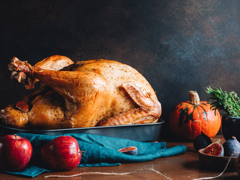 Festive table for Thanksgiving Holiday with whole roasted turkey with apple, pumpkin, figs and herbs in a mortar.