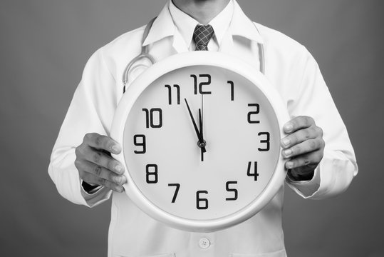 Hands of young Indian man doctor holding wall clock against gray background