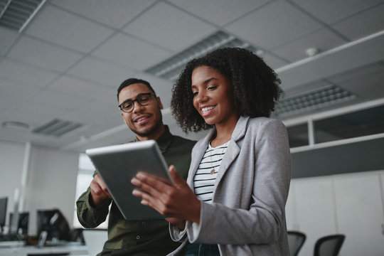 Portrait of smiling professional young African American businesswoman showing data on digital tablet to male colleague in office