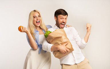 Couple Holding Grocery Shopping Bag Gesturing Yes On White Background
