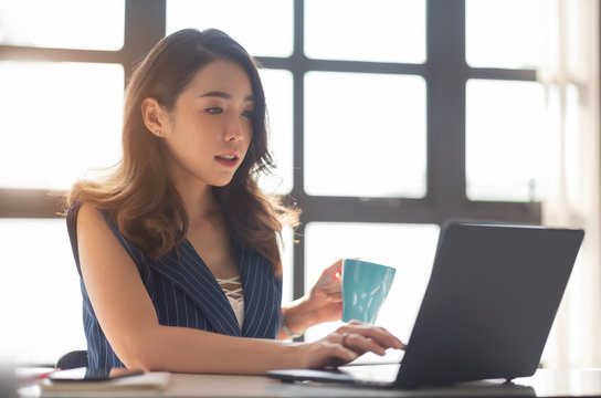Young Asian female sitting and using Laptop computer in the office.