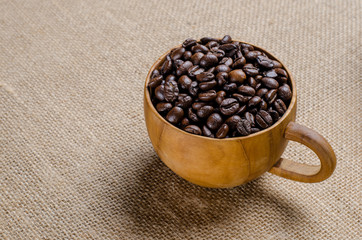 Wall Murals Coffee beans The coffee beans in the coffee wooden cup on the hessian sack for background , texture , copy text, Love coffee concept