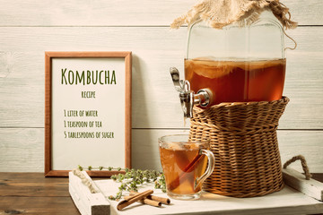 Fresh homemade kombucha fermented tea drink in a jar with faucet and in a cup on a white tray, the recipe for cooking in the frame, wooden background