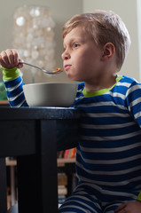 A cute little boy in striped pajamas eating cereal for breakfast at the dining room table