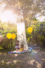 Two little girls playing outside and reading books in the yard in a shade tent with balloons