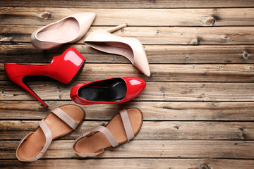 Different female shoes on brown wooden table