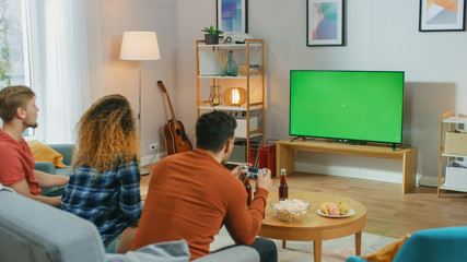 In the Living Room Three Friends Play Video Games on Green Chroma Key Screen, Using Controllers....