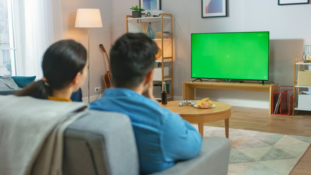Happy Couple Sitting At Home Watching Green Chroma Key Screen Television, Relaxing on a Couch. Couple Room Watching Sports Game, News, Sitcom TV Show or a Movie.