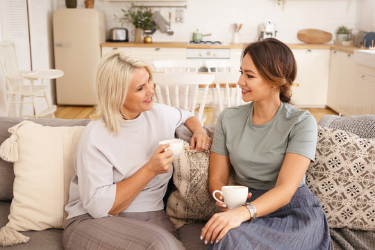 Sweet cozy portrait of beautiful mature female with blonde dyed hair holding cup, having coffee with her charming young daughter talking, sharing secrets or gossips, sitting on couch in living room