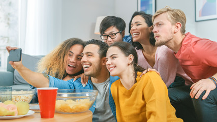At Home Diverse Group of Friends Doing Collective Selfie, Guy Holds Smartphone People Smile, Laugh and do Duck Lips.Young People Doing Live Stream of the Home Party.