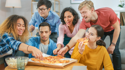 At Home Diverse Group Friends Watching TV Together, They Share Gigantic Pizza, Eating Tasty Pie Pieces. Guys and Girls Watching Comedy Sitcom or a Movie, Laughing and Having Fun Together.