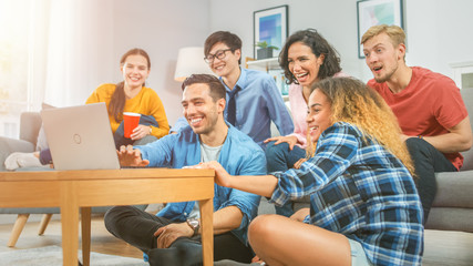 Diverse Group of Friends Use Laptop in the Living Room. Happy Beautiful Girls and Guys Doing Live Streaming. They Have Fun and Laugh. Cozy Room with Snacks and Drinks