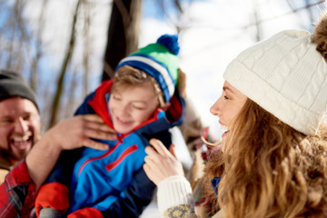 Mother and father enjoying playing in fresh snow during wintertime and tickling their son while laughing