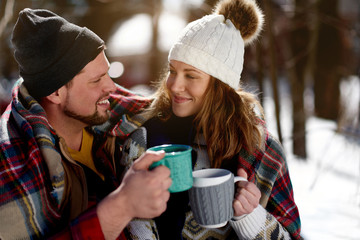 Papiers peints Chocolat Couple in love enjoying a tender moment in fresh snow during wintertime and drinking hot chocolate together