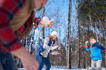 Happy family with son enjoying playing in fresh snow during wintertime and having a snowball fight