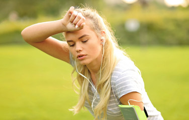 Tired female runner in the park taking a break - Sporty woman breathing and resting after outdoor sport activity