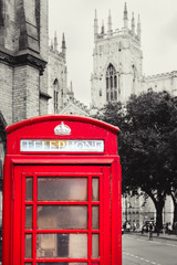 Old british red phone booth with the York Cathedral on the background - Background in black and white